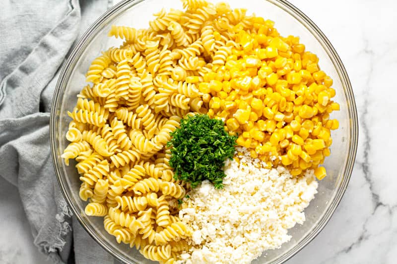 Large glass bowl filled with ingredients to make Mexican street corn pasta salad