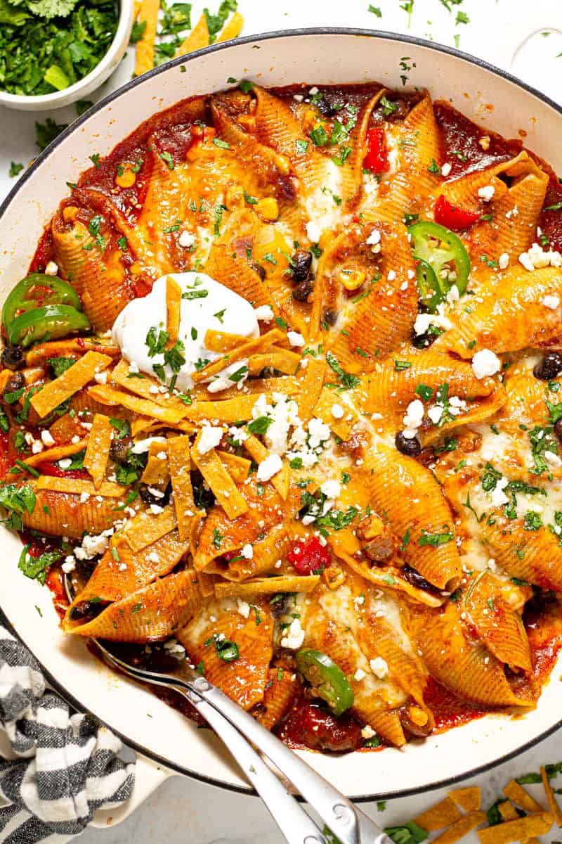 Overhead shot of a large white pan filled with Mexican stuffed shells garnished with sour cream and fresh cilantro