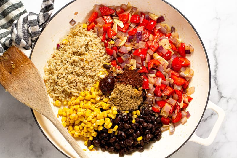 Large white pan filled with sauteed veggies corn black and quinoa