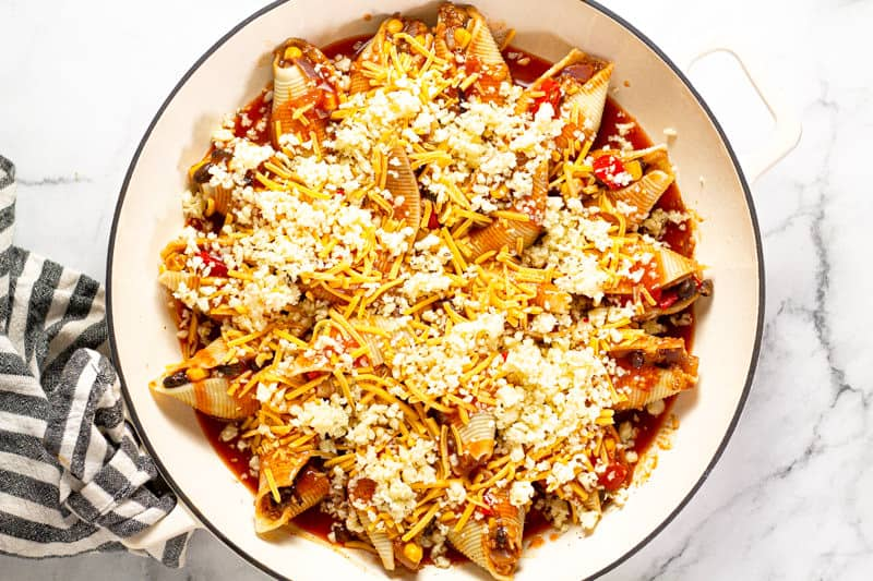 Large white pan filled with Mexican stuffed shells topped with shredded cheese