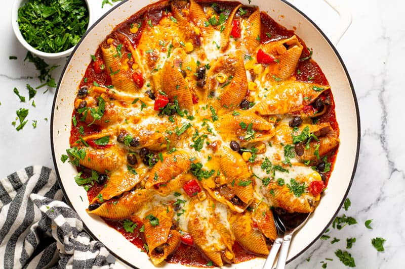 Large white pan filled with homemade Mexican stuffed shells fresh from the oven
