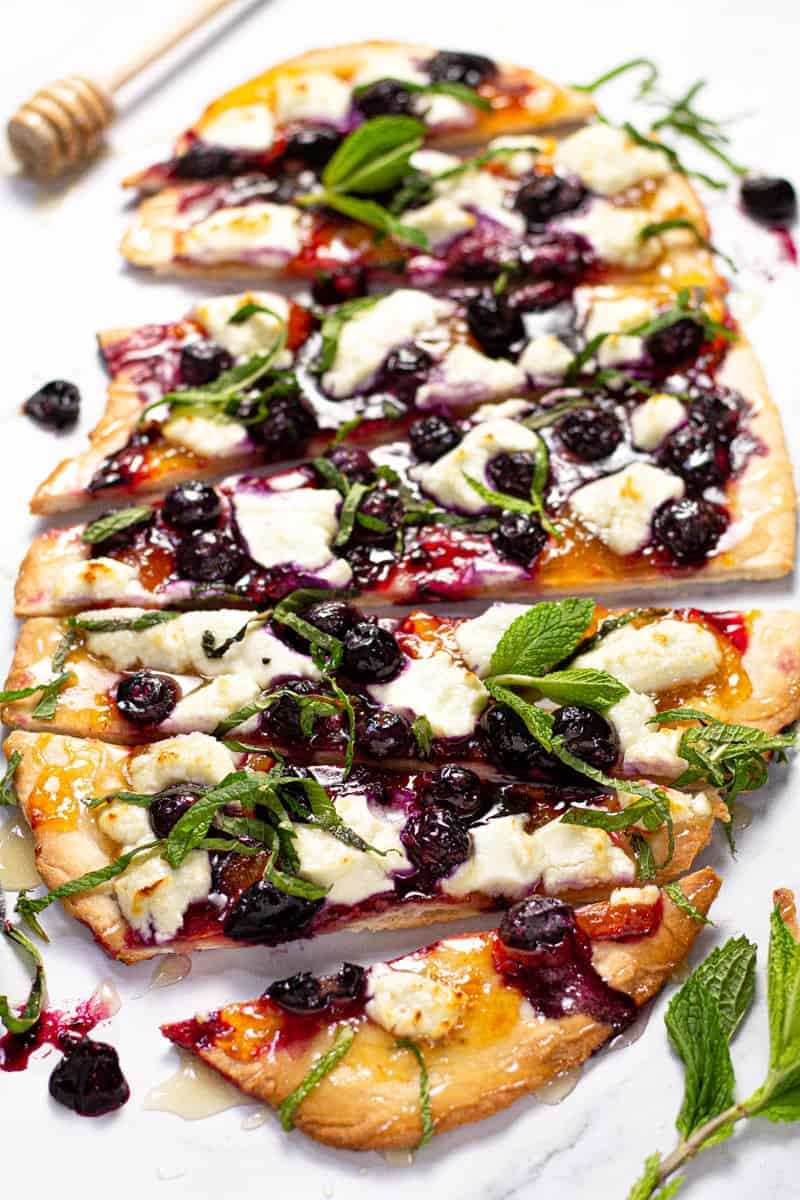 Close up shot of a homemade blueberry goat cheese flatbread garnished with fresh mint leaves