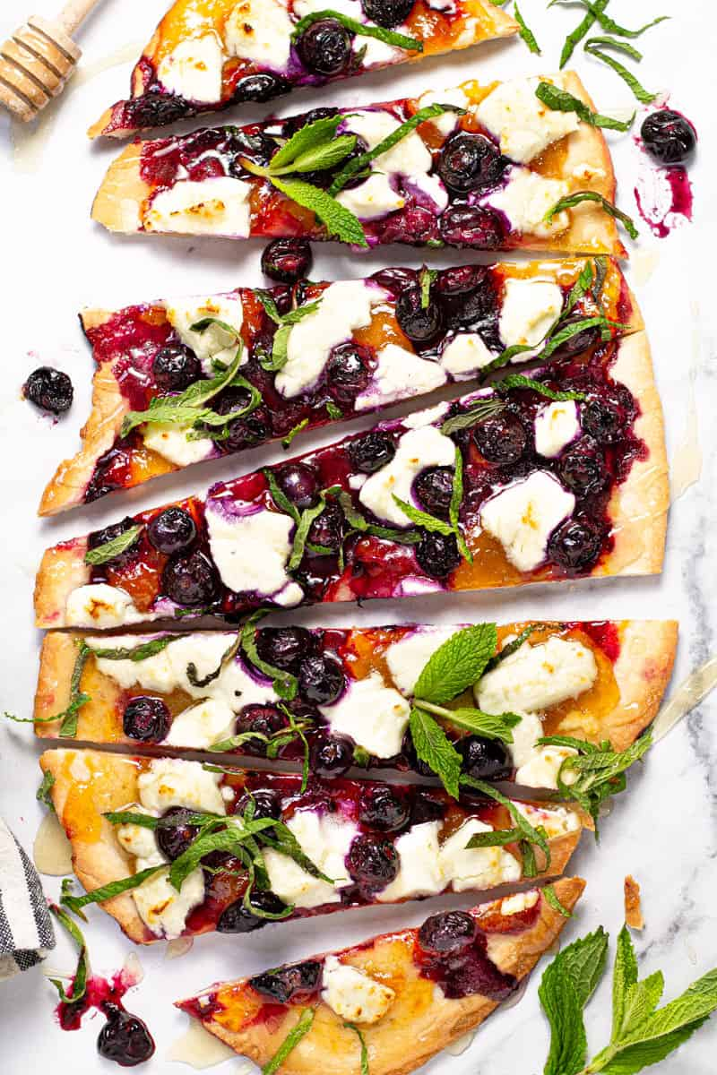 Overhead shot of a homemade blueberry goat cheese flatbread garnished with fresh mint leaves