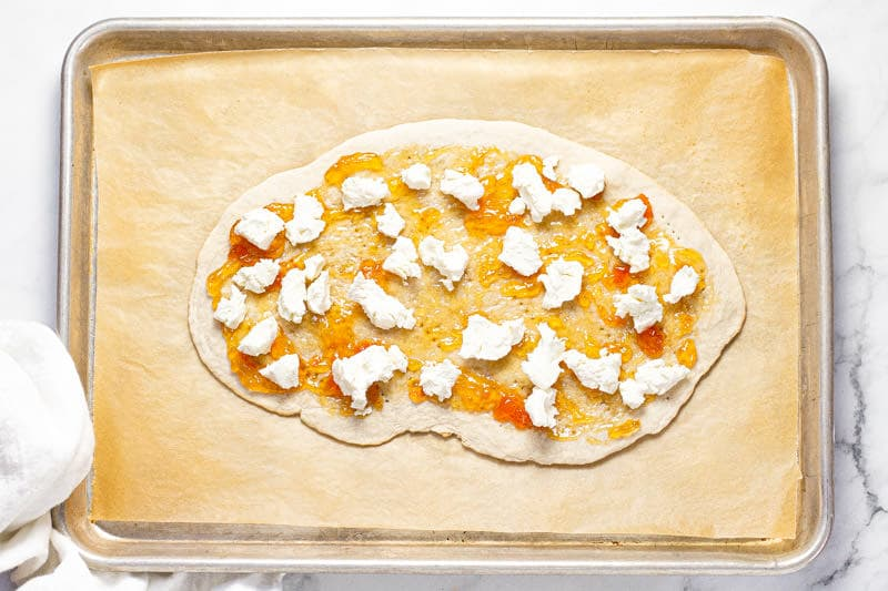 Overhead shot of a baking sheet with flatbread dough spread with apricot jam