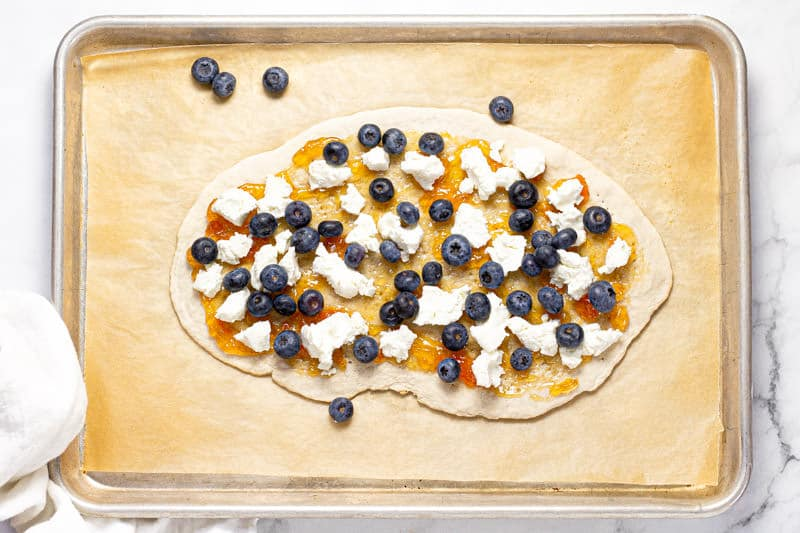 Overhead shot of a baking sheet with blueberry goat cheese flatbread