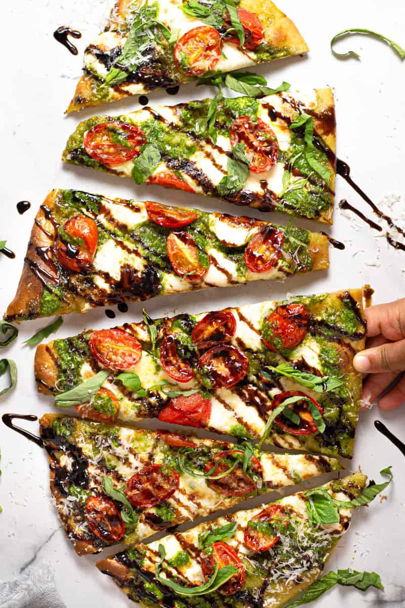 Overhead shot of a Caprese flatbread garnished with fresh basil and balsamic glaze