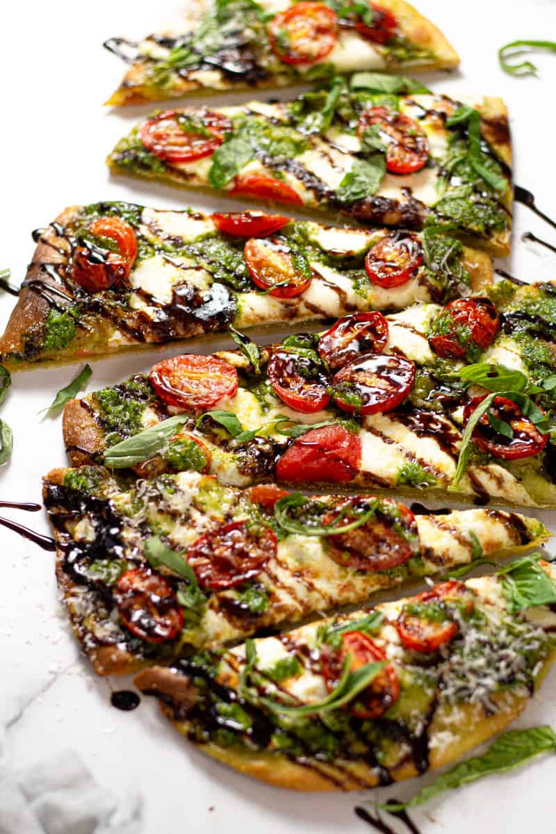 Close up shot of a Caprese flatbread garnished with fresh basil and balsamic glaze