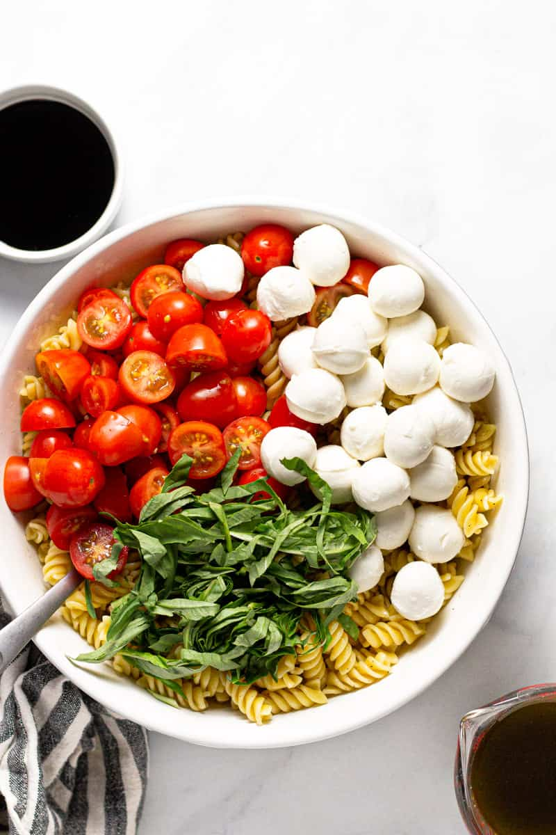 Large white bowl filled with ingredients to make a Caprese pasta salad