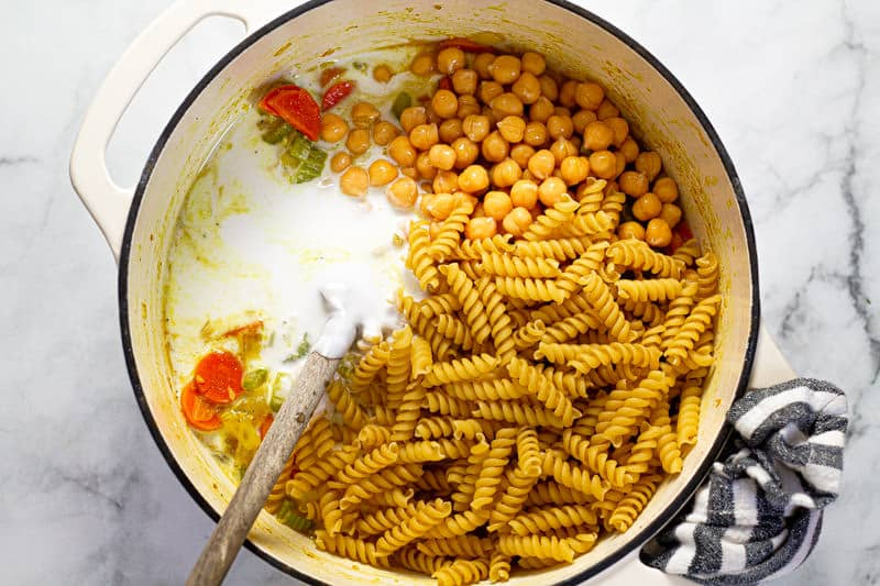 Large white pot filled with coconut milk chickpeas and pasta