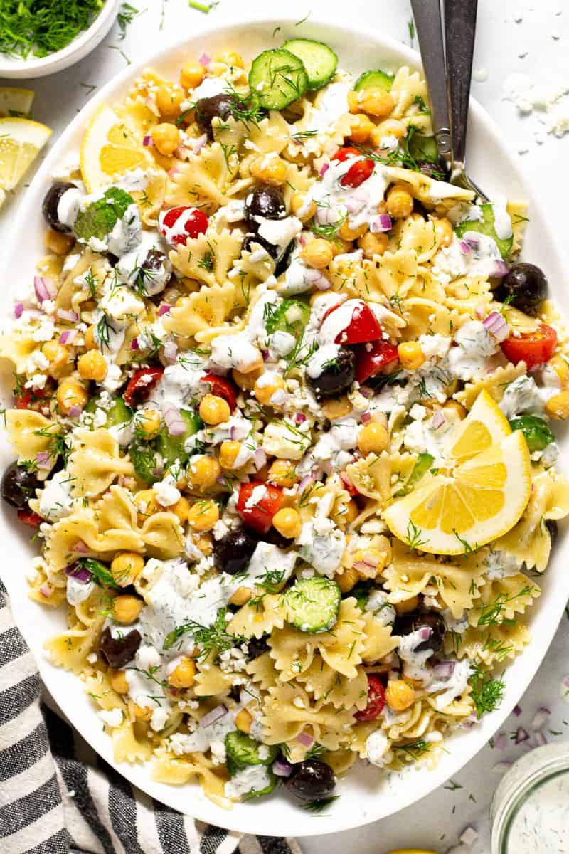 Overhead shot of a large white platter of Greek pasta salad drizzled with yogurt sauce
