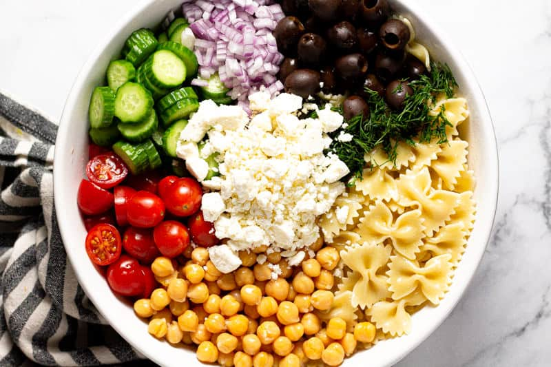 Overhead shot of a large white bowl filled with ingredients to make chickpea pasta salad