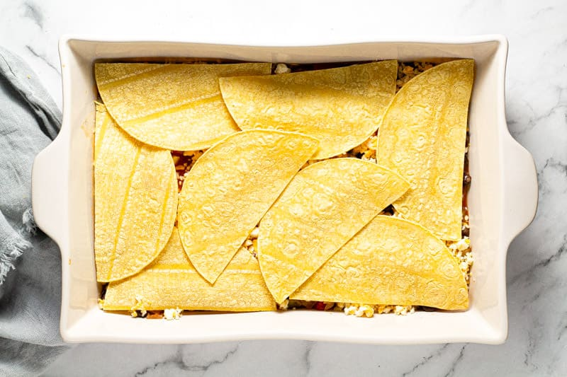 Large white baking dish filled with ingredients to make enchilada casserole