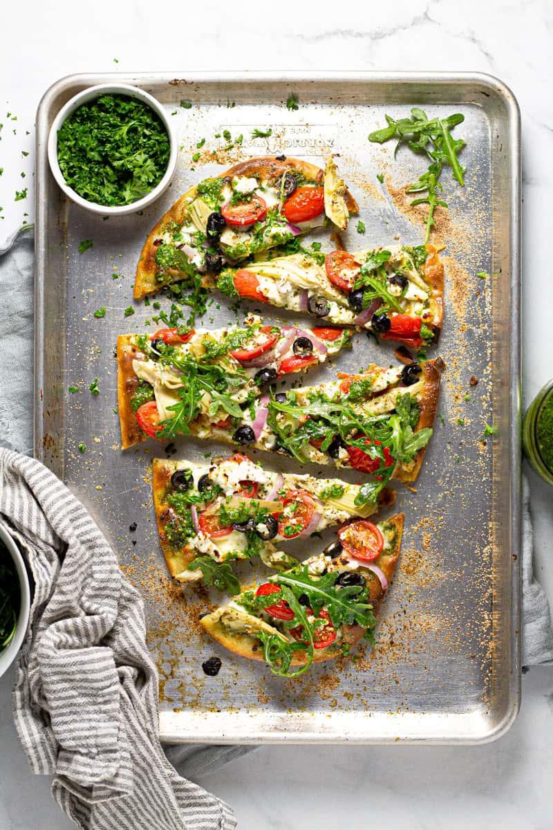 Overhead shot of a Mediterranean flatbread pizza garnished with fresh parsley