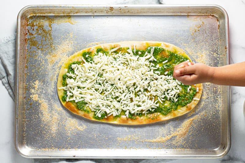 Small hand adding shredded mozzarella to flatbread pizza