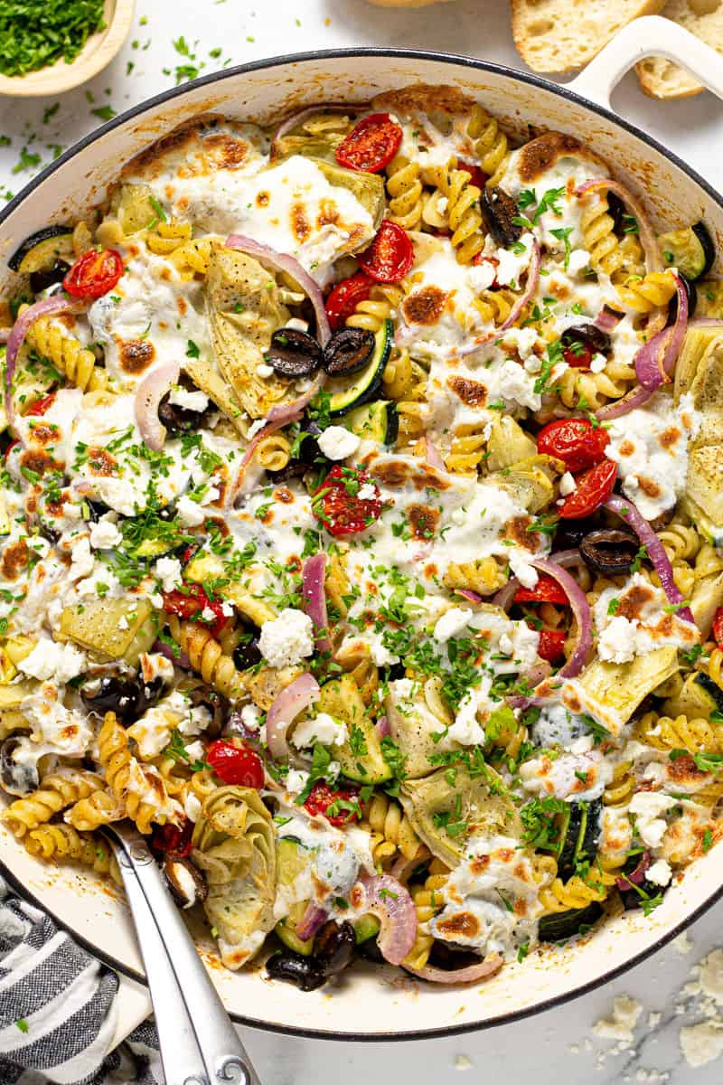 Overhead shot of a pan filled with baked Mediterranean pasta garnished with fresh parsley