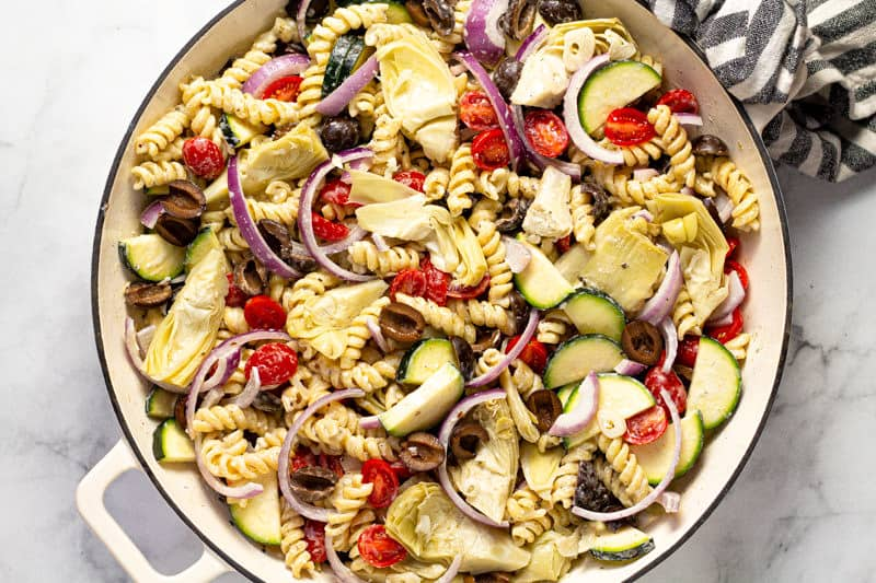 Zucchini olives red onion tomato and artichoke hearts mixed with pasta and feta sauce