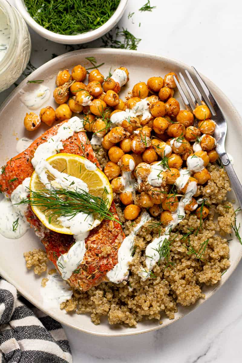 Overhead shot of a white plate filled with roasted chickpeas, quinoa, and salmon drizzled with yogurt sauce