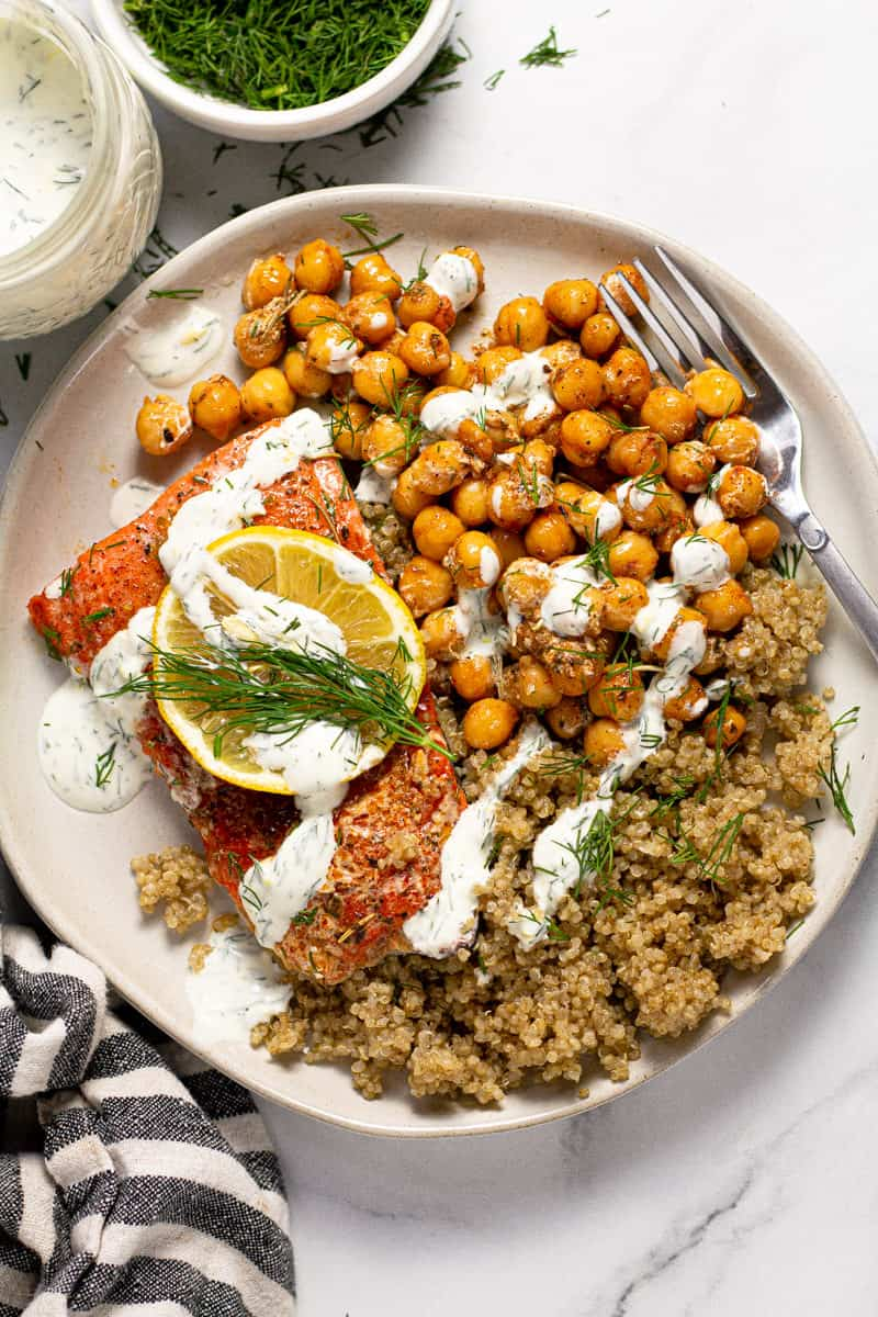 Overhead shot of a white plate filled with roasted chickpeas, quinoa and salmon drizzled with yogurt sauce