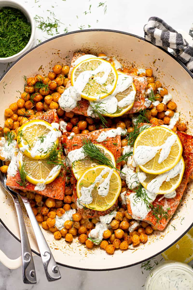 Overhead shot of a white pan filled with Mediterranean baked salmon and roasted chickpeas drizzled with yogurt sauce