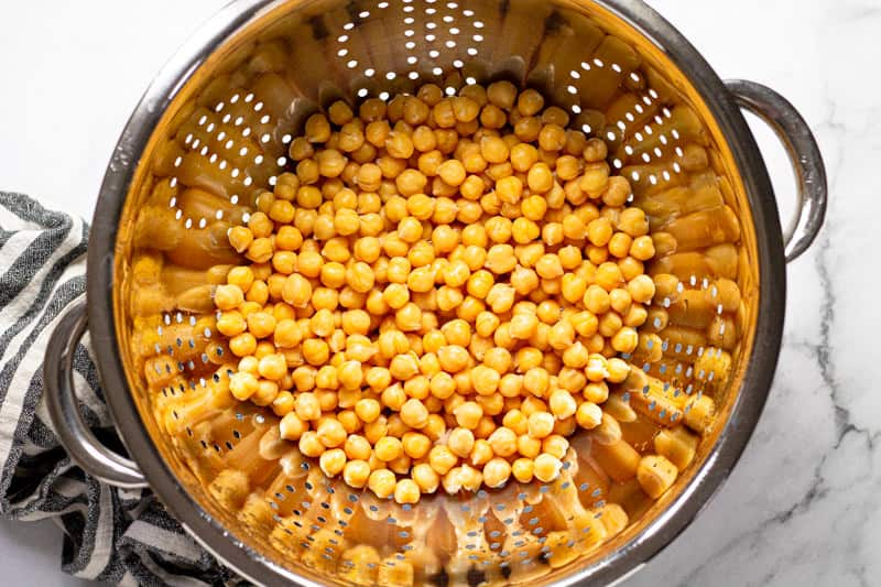 Overhead shot of a silver strainer with canned chickpeas in it