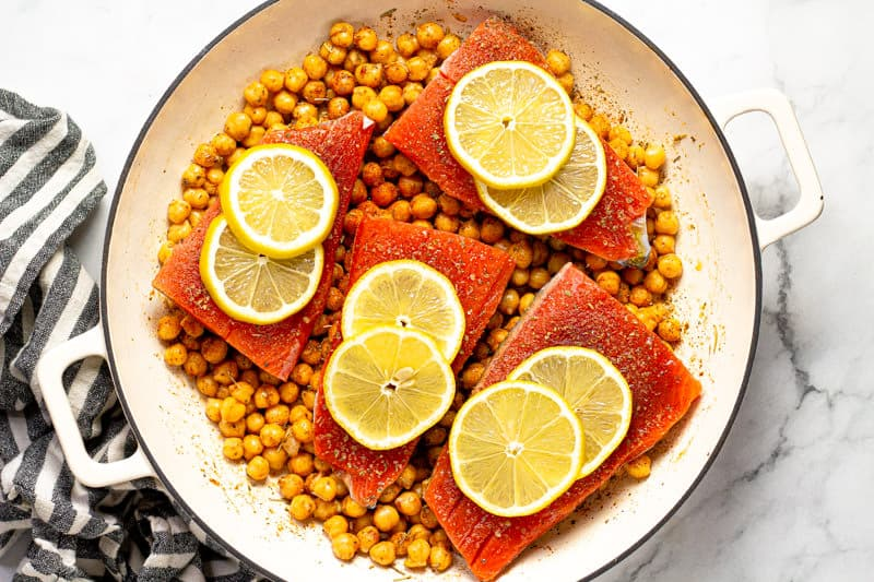 Large white pan filled with seasoned garbanzo beans and 4 salmon fillets with lemon slices on top