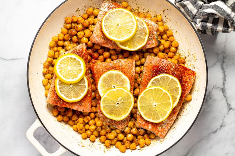 Large white pan filled homemade baked Mediterranean salmon
