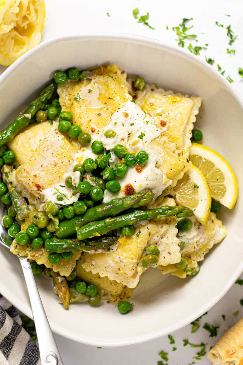 Overhead shot of a large white bowl filled with spring ravioli with asparagus peas and cheese