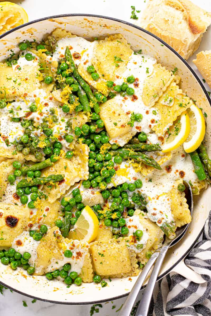 Overhead shot of a large white pan filled with spring ravioli with asparagus peas and cheese