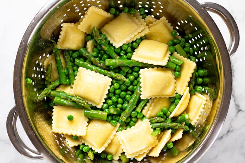 Overhead shot of a metal strainer filled with cooked ravioli peas and asparagus
