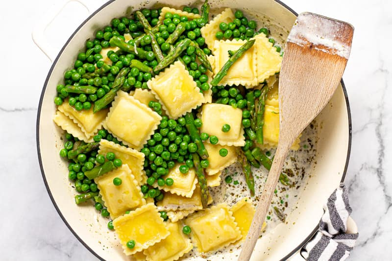 Large white pan with a creamy herb and garlic goat cheese sauce with ravioli peas and asparagus