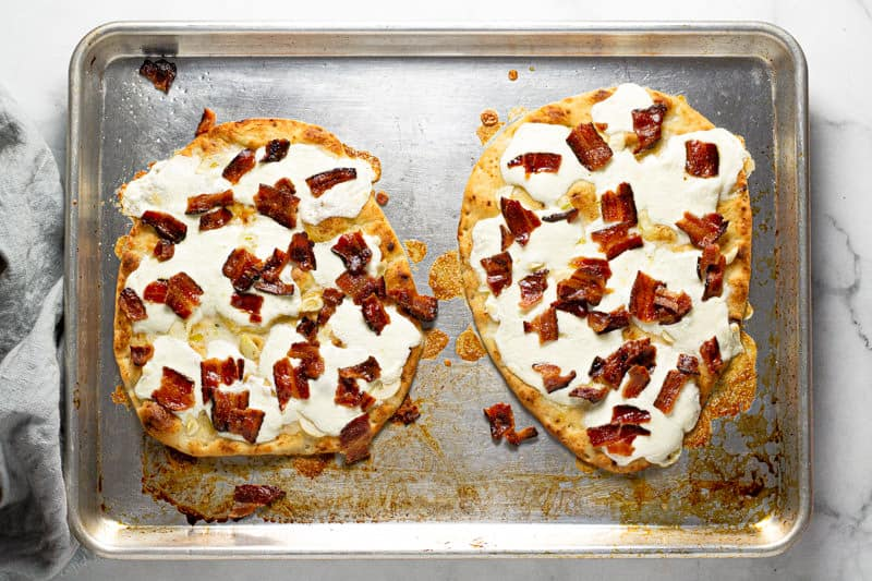 Sheet pan with two flatbreads with sliced garlic and fresh mozzarella and bacon on them