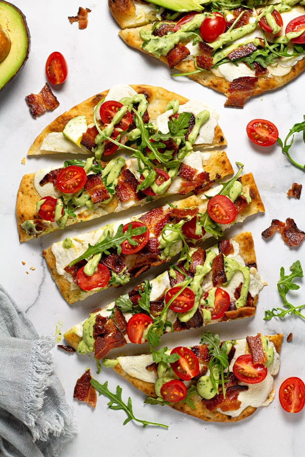 Overhead shot of BLT flatbread garnished with avocado cream sauce and fresh arugula