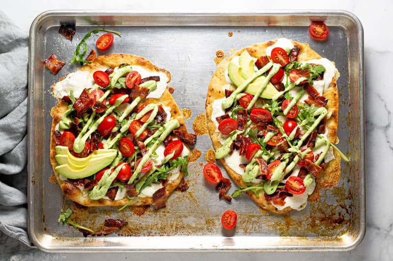 Overhead shot of a baking sheet with two California BLT flatbreads garnished with avocado sauce and arugula