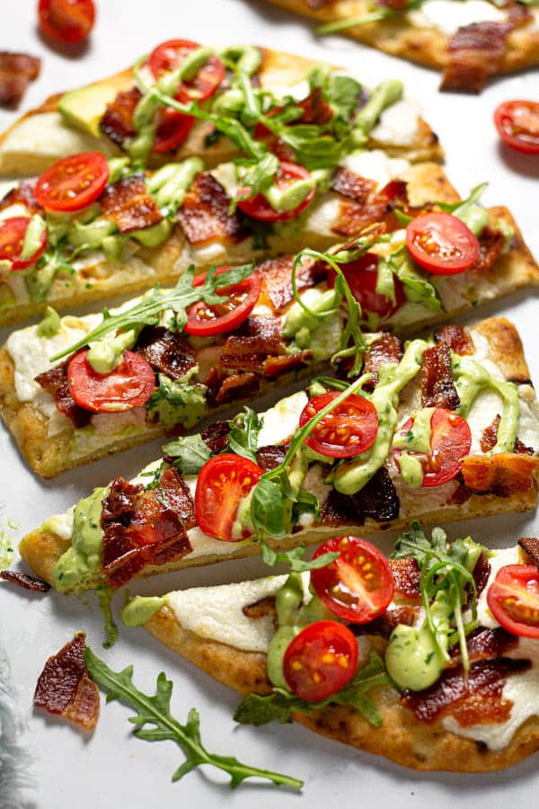 Close up shot of BLT flatbread garnished with avocado cream sauce and fresh arugula