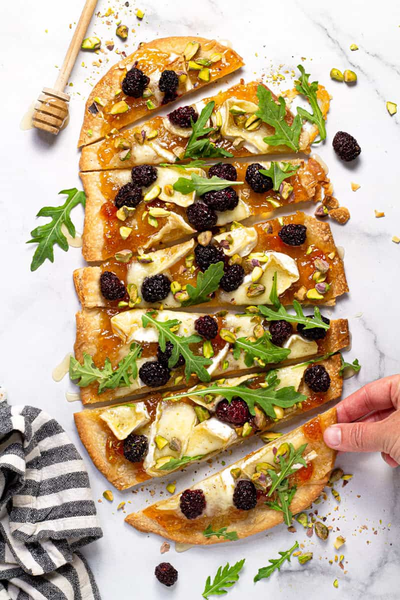 Brie and blackberry flatbread garnished with arugula on a white marble counter top