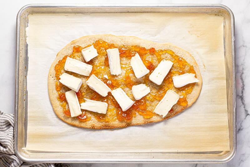 Baking sheet with a flatbread crust spread with apricot preserves and brie