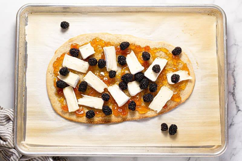 Baking sheet with a flatbread crust spread with apricot preserves brie and blackberry