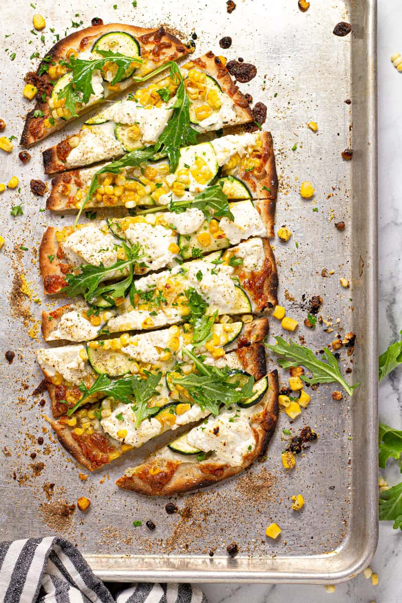 Overhead shot of a vegetable flatbread on a baking sheet sliced and ready to eat