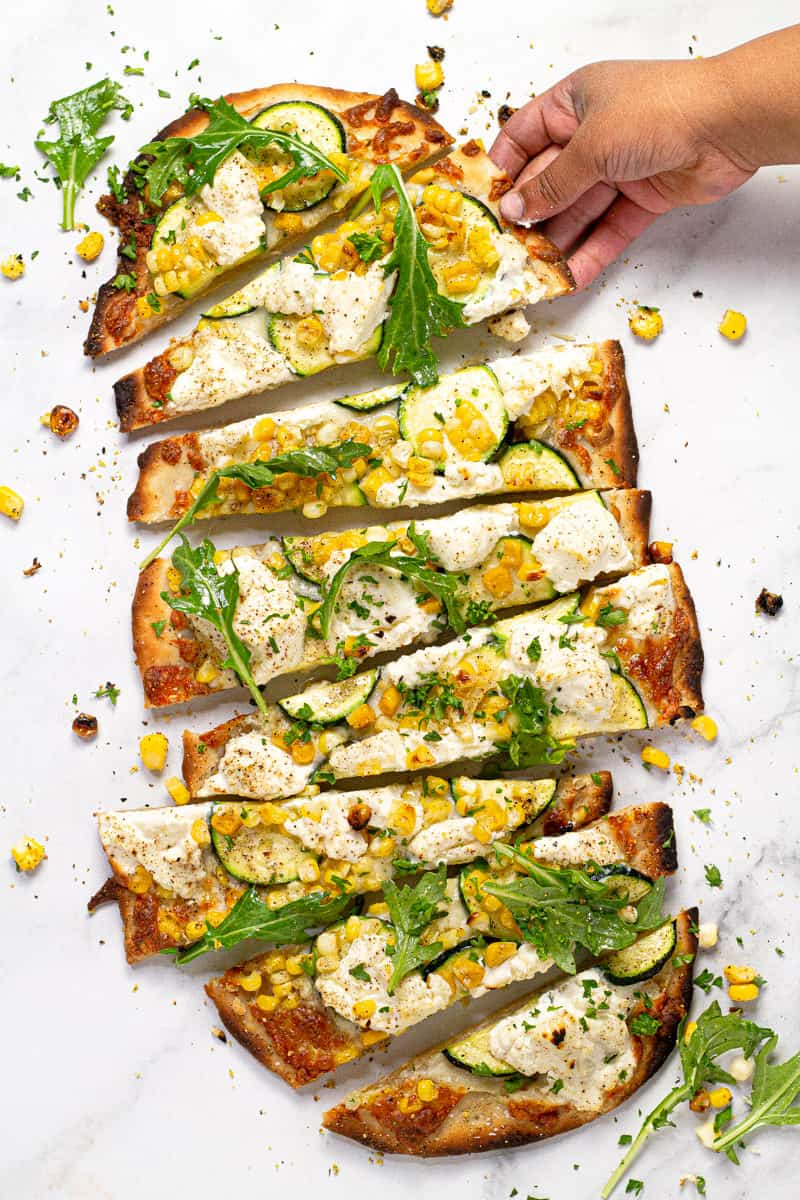 Overhead shot of a vegetable flatbread on a white marble counter top sliced and ready to eat
