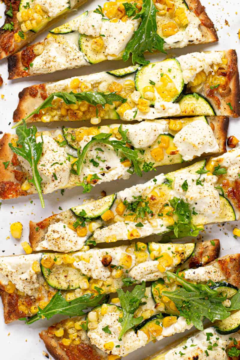 Close up of a vegetable flatbread on a white marble counter top sliced and ready to eat