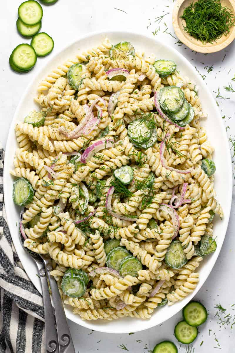 Large white platter filled with creamy vegan cucumber pasta salad