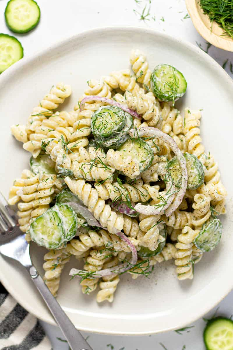 Overhead shot of a plate with creamy cucumber pasta salad garnished with dill