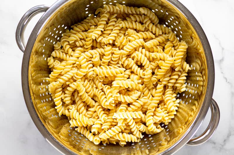 Metal strainer with cooked al dente noodles in it