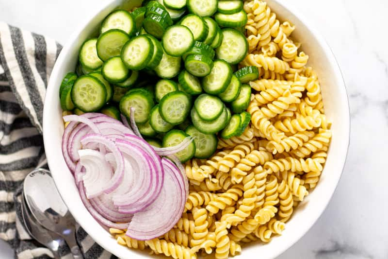 Large white bowl with cooked pasta cucumbers and red onions in it