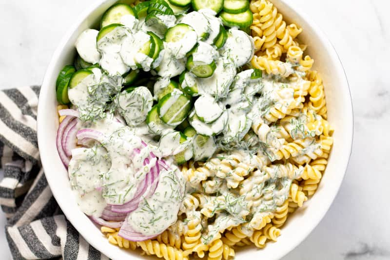 Large white bowl with cooked pasta cucumbers and red onions drizzled with creamy vegan dressing