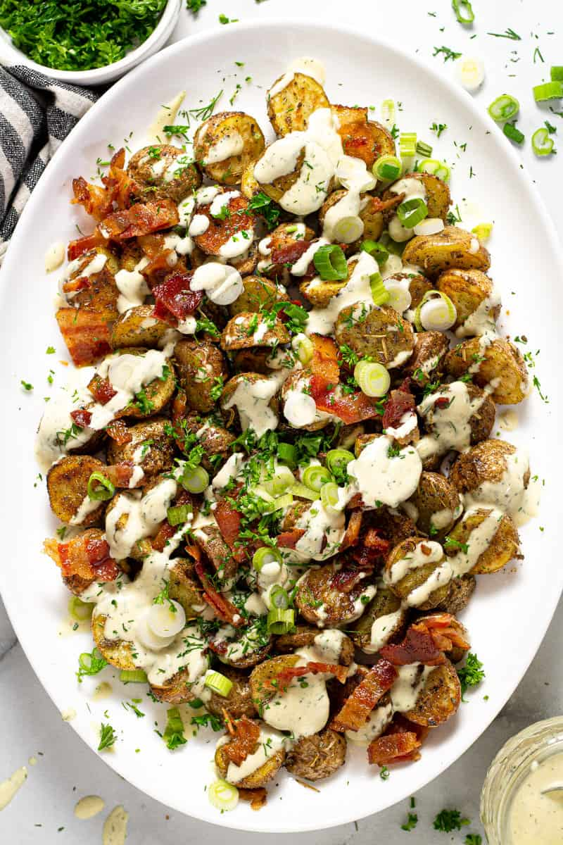 Overhead shot of a large serving platter with roasted potato salad garnished with bacon and parsley