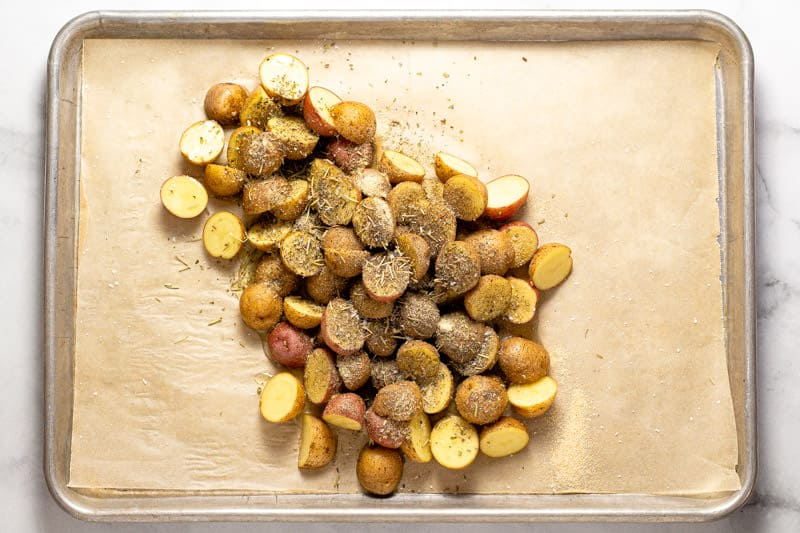 A parchment lined baking sheet with sliced potatoes seasoned with oil and dried herbs