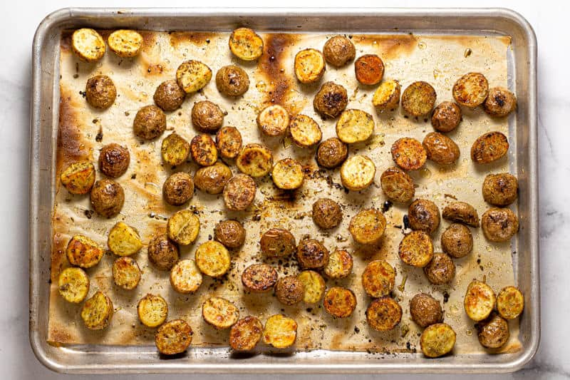 A parchment lined baking sheet with roasted potatoes seasoned with oil and dried herbs