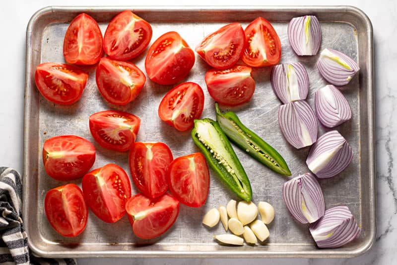 Baking sheet with quartered tomatoes onions jalapeno and cloves of garlic on it