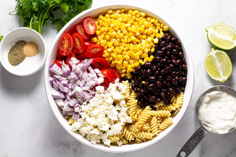 Overhead shot of a large white bowl filled with ingredients to make pasta salad
